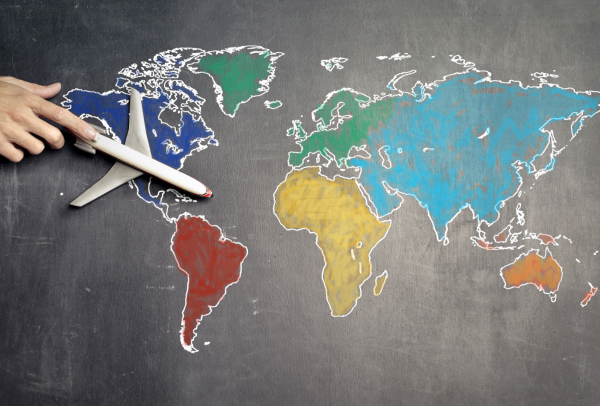 Hand guiding airplane across world map drawn on chalkboard