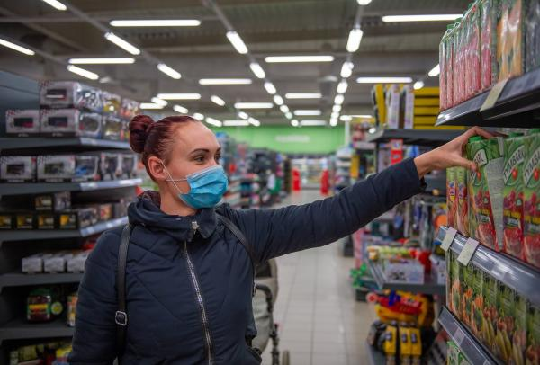 A photo of a woman wearing a face mask and grabbing juice off the shelf of a supermarket