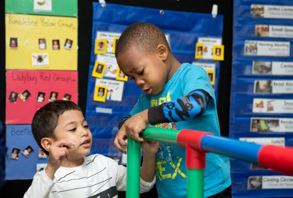 Preschool students build a structure from plastic interlocking tubes.