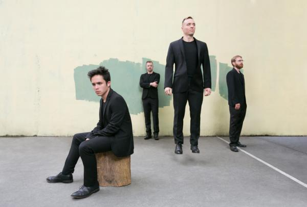 Members of the JACK Quartet posing in front of a yellow wall.